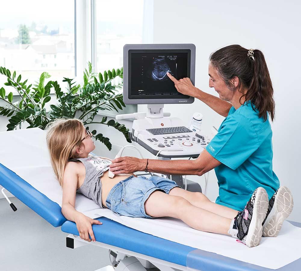 Ärztin zeigt Mädchen die Daten auf dem Bildschirm