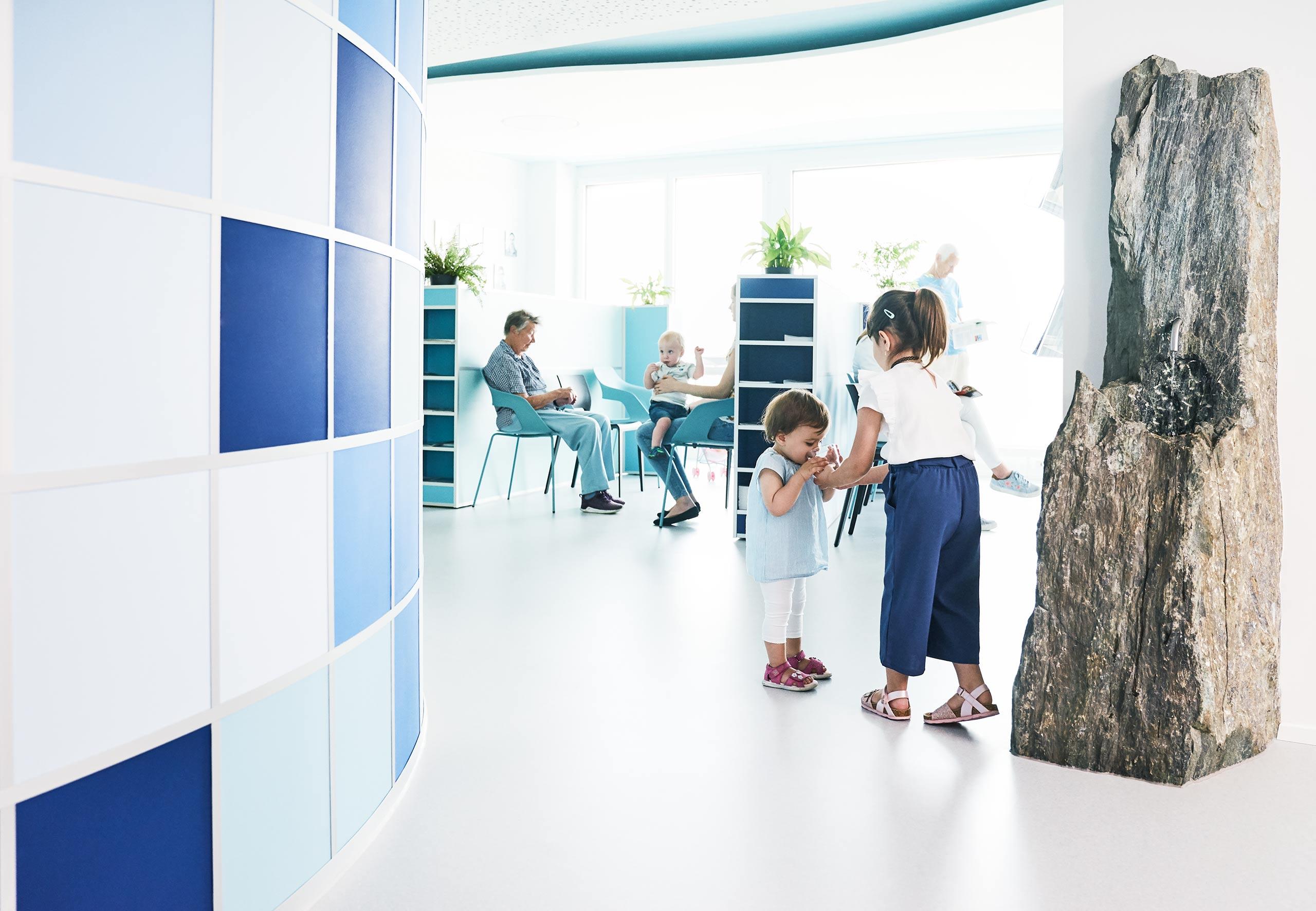 Empfangsbereich der Praxis, spielende Kinder, ein Brunnen